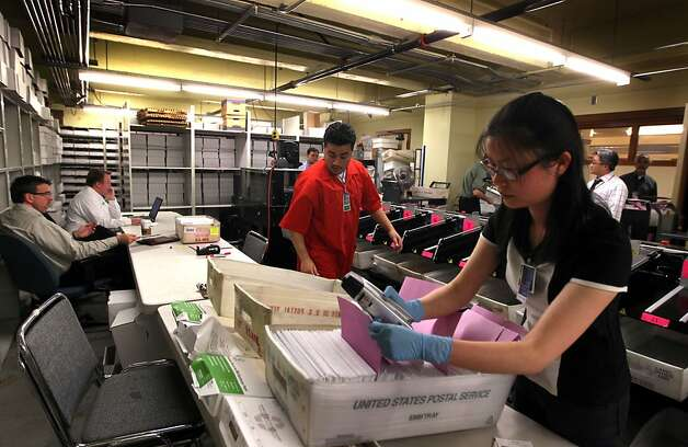 City employees Elliot Bottel in red and Shuya Li sort mail In ballots in the basement of San Francisco City Hall Tuesday November 8, 2011 Photo: Lance Iversen, The Chronicle