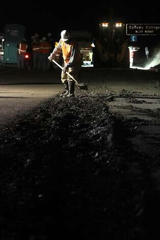 A worker clears mud from the side of Interstate 280 where a burst in a PG&E line during a hydrostatic pressure test sent earth down on the freeway on Sunday, Nov. 6, 2011, in Woodside, Calif. Photo: Mathew Sumner, Special To The Chronicle