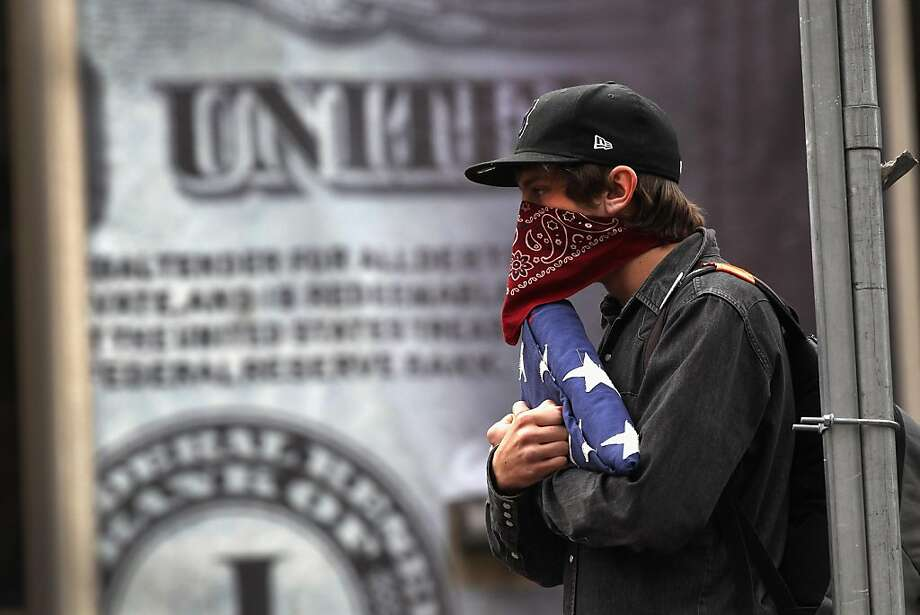 DENVER, CO - NOVEMBER 05:  An Occupy Denver protester holds an American flag during a march outside the Denver Federal Reserve building on November 5, 2011 in Denver, Colorado. Hundreds of demonstrators marched in a peaceful protest, denouncing the Federal Reserve and urging customers to close their accounts with large banks and deposit their funds into local credit unions.  (Photo by John Moore/Getty Images) Photo: John Moore, Getty Images