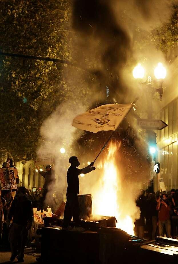 An Occupy Oakland protester waves a flag next to a bonfire in Oakland, Calif., Thursday, Nov. 3, 2011. (AP Photo/Jeff Chiu) Photo: Jeff Chiu, AP