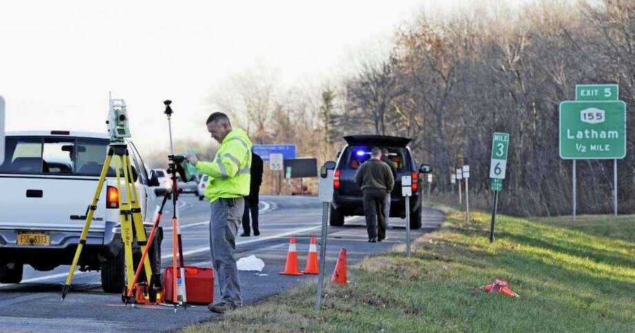 A NYSP Investigator starts the process of determining the cause of a fatal accident at the on-ramp to I 87 at Exit 4 in Colonie, N.Y. Nov. 30, 2011.  The cones mark the location of the deceased person on the side of the road. (Skip Dickstein/Times Union) Photo: Skip Dickstein / 2011