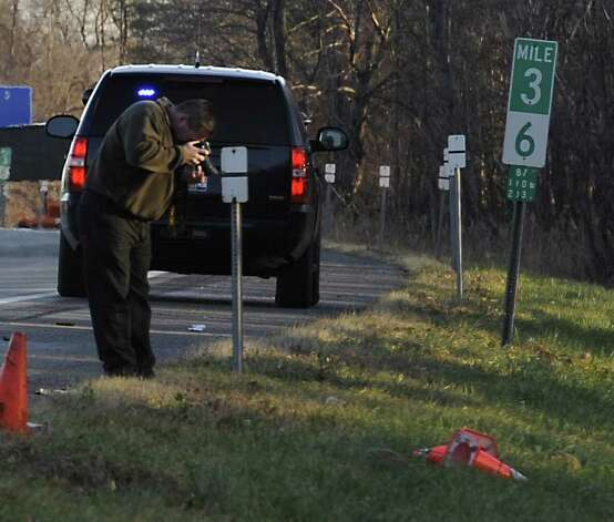 A NYSP Investigator photographs the scene during the process of determining the cause of a fatal accident at the on-ramp to I 87 at Exit 4 in Colonie, N.Y. Nov. 30, 2011.  (Skip Dickstein/Times Union) Photo: Skip Dickstein / 2011