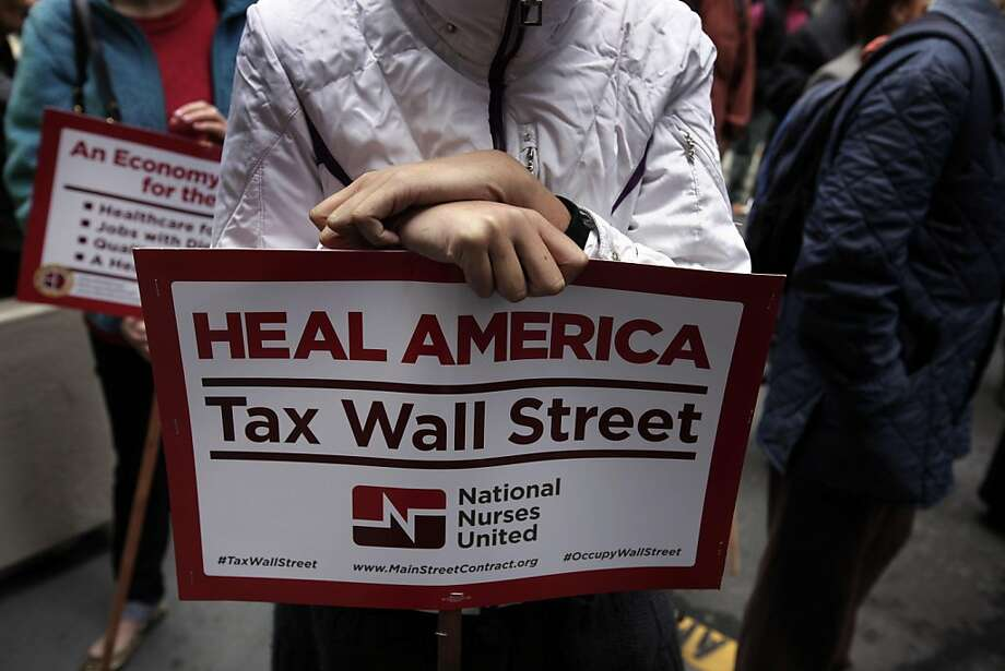 Miran Istina, 18 years old, holds a protest sign as she gathers with other Occupy San Francisco members and the nurses union to protest health care and walls street, outside the Wells Fargo Bank on Montgomery Street , Thursday Nov. 3, 2011, in San Francisco, Calif.  Ran on: 11-04-2011 A nurse holds a pro-tax sign outside the Wells Fargo Bank on Montgomery Street in S.F. Photo: Lacy Atkins, The Chronicle