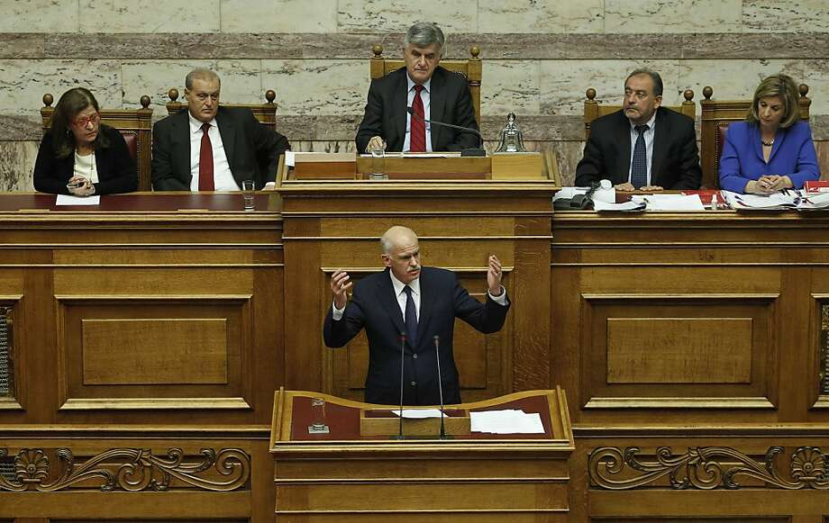 Greek Prime Minister George Papandreou speaks during a parliament session in Athens, Thursday, Nov. 3, 2011. Papandreou abandoned his explosive plan to put a European rescue deal to popular vote Thursday, keeping his government alive _ but passionate squabbling in Athens left the country's solvency in doubt and the eurozone in turmoil. Greek Prime Minister reversed course after a rebellion within his own Socialist party over the referendum, but ignored repeated calls to resign and call elections. (AP Photo/Petros Giannakouris) Photo: Petros Giannakouris, AP
