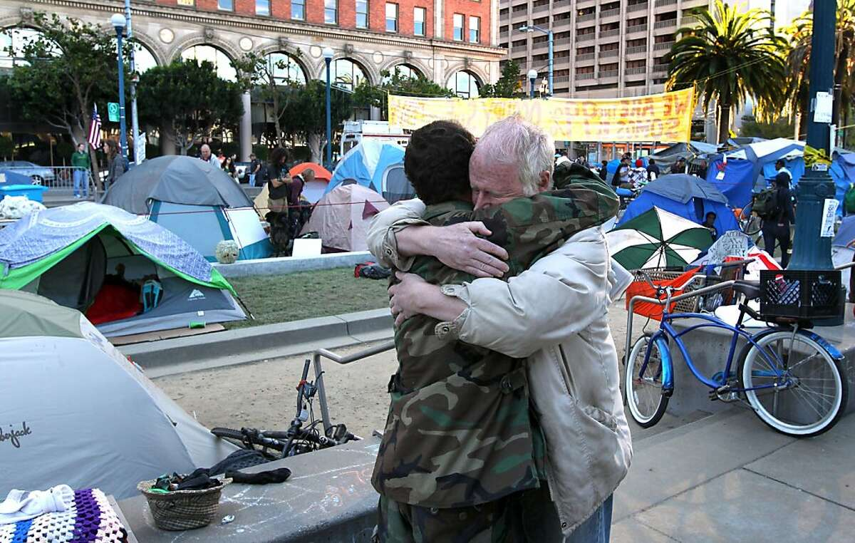 James Jennison left hugs an old friend of 13 years who declinded to give his name, Both men are taking part in Occupy San Francisco in Justin Herman Park Thursday Oct 27, 2011.