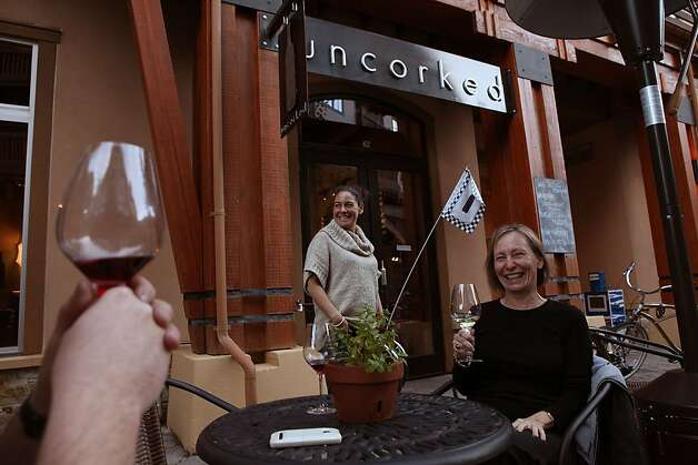 Roy Hage (left, not seen) having Talisman Pinot Noir  from Sonoma Coast,  owner Kali Kopley (middle), and Laura Hum (right) having Venge Vineyards, Napa Valley, white blend at Uncorked in Squaw Valley , Calif., on Wednesday, October 12, 2011. Photo: Liz Hafalia, The Chronicle
