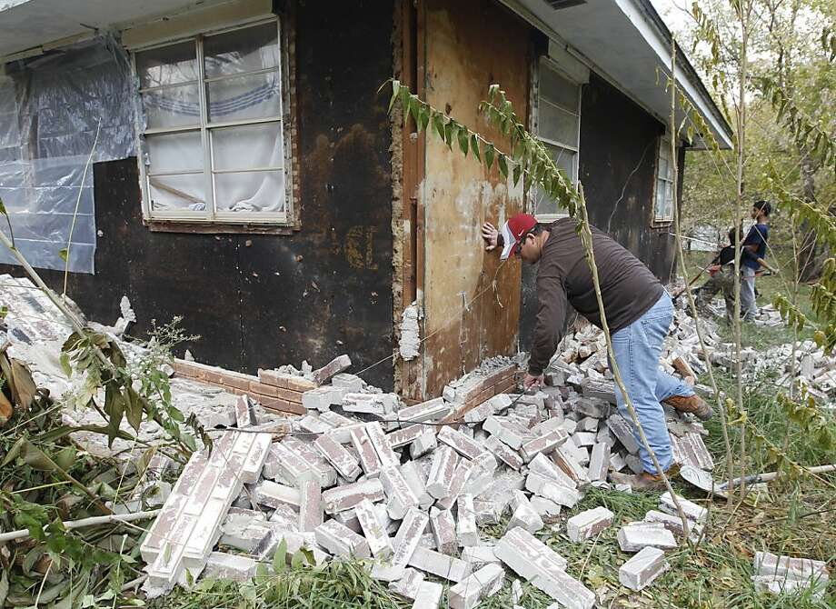 Chad Devereaux works at cleaning up the bricks that fell from three sides of his in-laws home in Sparks, Okla., Sunday, Nov. 6, 2011, after two earthquakes hit the area in less than 24 hours. (AP Photo/Sue Ogrocki) Photo: Sue Ogrocki, AP