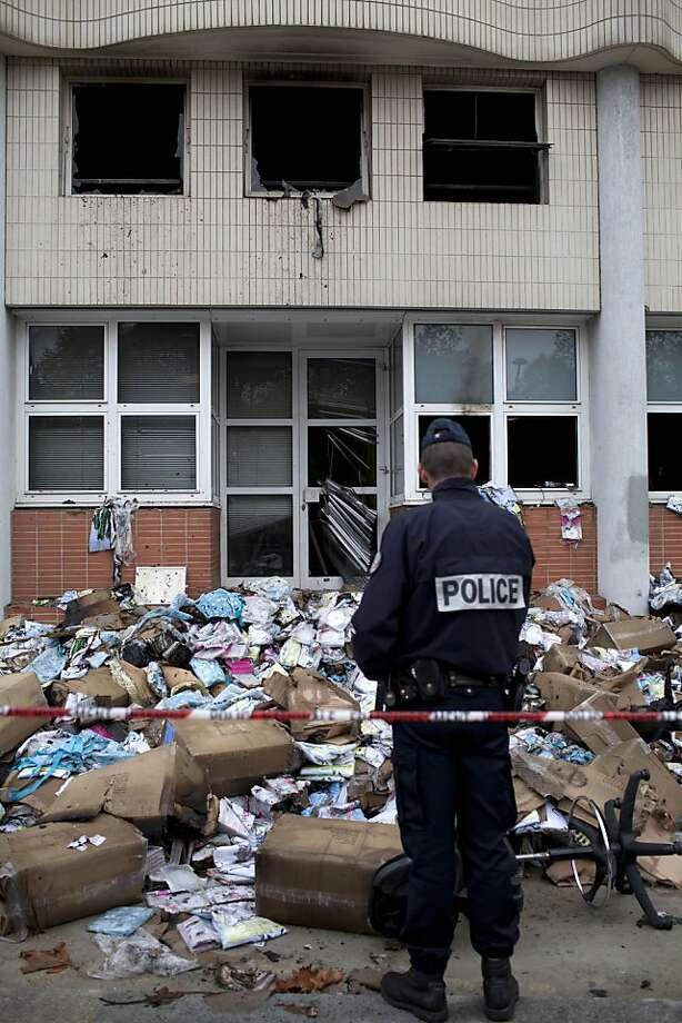 """A police officer stands in front of the headquarters of satirical French newspaper Charlie Hebdo, that """"invited"""" the Prophet Muhammad as a guest editor this week, in Paris, Wednesday, Nov. 2, 2011. A police official said the fire broke out overnight at the offices of Charlie Hebdo, and the cause remains unclear. No injuries were reported. The official spoke on condition of anonymity because an investigation into the fire is under way. (AP Photo/Thibault Camus) Photo: Thibault Camus, AP"""