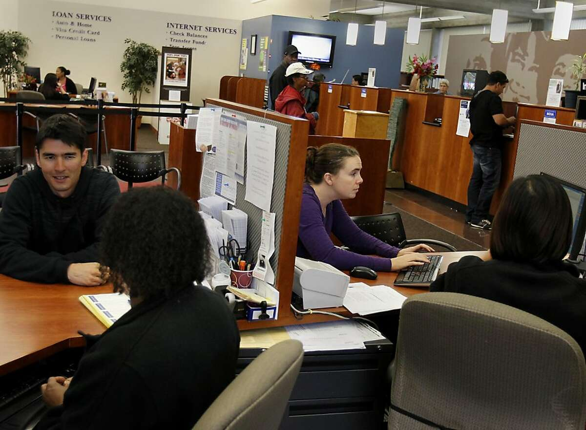 Sasha Hood (right) types in information for her new accounts at the credit union. She is shutting down her Wells Fargo accounts. Credit Unions like the Cooperative Center Federal Credit Union in Berkeley, Calif. are seeing more new customers transferring accounts from the more traditional big banks.