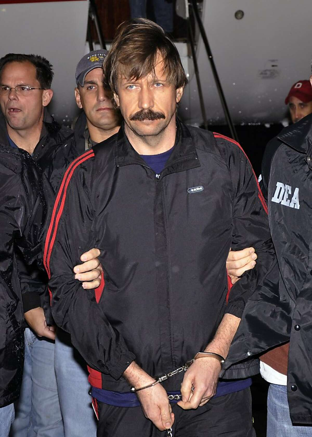 FILE - This Nov. 16, 2010, file photo, provided by the Drug Enforcement Administration shows Viktor Bout being led off a flight from Bangkok to New York during his extradition to face trial on charges of transporting tons of weapons that inflamed violence across the world's war zones. A jury in New York found the Russian arms dealer guilty on all counts Wednesday, Nov. 2, 2011. (AP Photo/Drug Enforcement Administration, File)