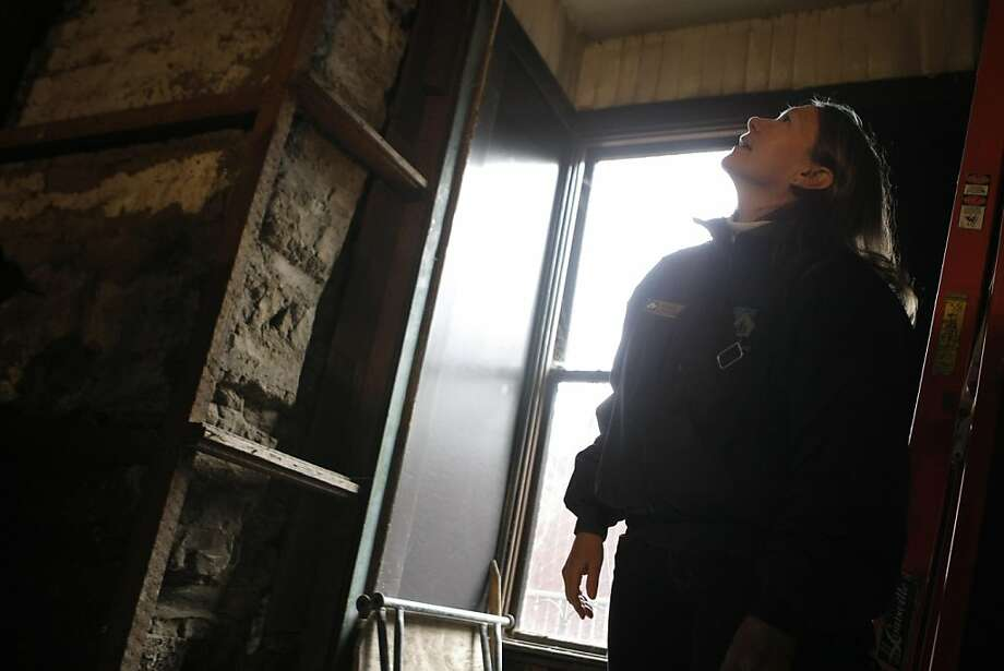 Conservators Christina Wallace looks upwards toward seismic restoration work being done on Building 50, also known as the Officer's Club, in the Presidio in San Francisco , Calif., on Saturday, Nov. 5, 2011. Photo: Dylan Entelis, The Chronicle