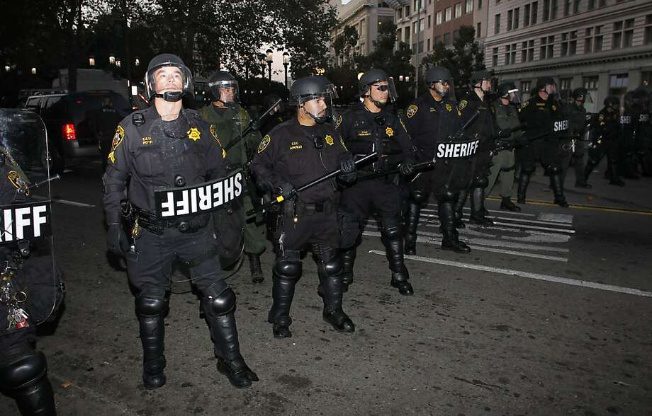 San Francisco Shefiff deputies guard Frank Ogawa Plaza at Broadway and 14th street, as the  Occupy Oakland protesters continue their cause as they march along the streets of downtown Oakland, Ca., on Tuesday October 25, 2011. Photo: Michael Macor, The Chronicle
