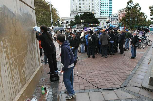 Members of Occupy Oakland and concerned citizens pitch in to clean up graffiti on a Bart elevator next to a prerss conferance to explain that last night's violence was not their doing Thursday, November 3, 2011 Photo: Lance Iversen, The Chronicle