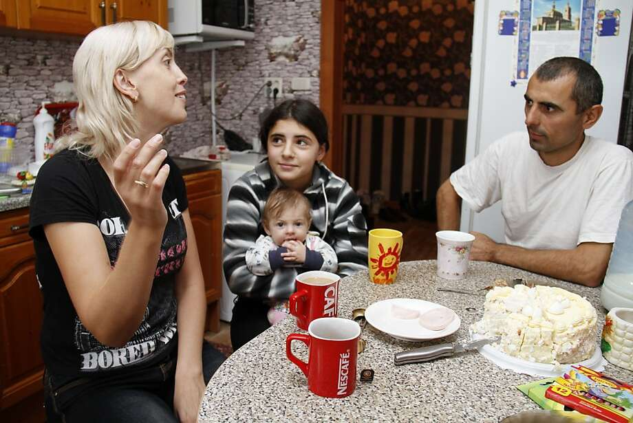 A picture taken on September 2011 shows Yuliya Belyaeva (L) as she speaks with Irina (C) and her biological father Naimat (R) in Kopeisk. Two families in Russia are suing their local maternity hospital for giving them the wrong babies 12 years ago.     AFP PHOTO/ KOMSOMOLSKAYA PRAVDA/ VALERY ZVONAREV (Photo credit should read VALERY ZVONAREV/AFP/Getty Images) Photo: Valery Zvonarev, AFP/Getty Images