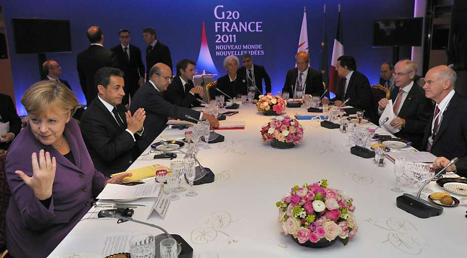 France's President Nicolas Sarkozy, second left, and Germany's Chancellor Angela Merkel, left, meet with Greece's Prime Minister George Papandreou, right, for crisis talks before a G20 summit of major world economies in Cannes, France on Wednesday, Nov. 2, 2011. (AP Photo/Philippe Wojazer/Pool) Photo: Philippe Wojazer, AP