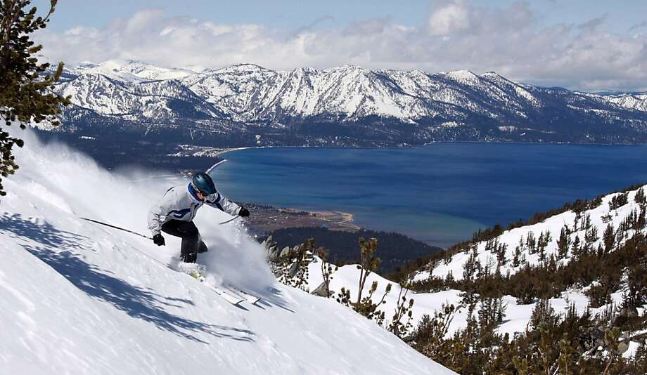 With Lake Tahoe as a backdrop, a skier kicks up some powder at Heavenly Ski Resort, Wednesday, April 14, 2010 in South Lake Tahoe, Calif.  New snow and favorable temperatures have enabled mid-winter snow conditions into mid-April on several Sierra ski mountains.  Great conditions notwithstanding, some resorts will close this week although Heavenly has extended their season until April 25.  (AP Photo/Dino Vournas) Photo: Dino Vournas, AP