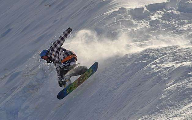 A snowboarder catches some air at Northstar-at-Tahoe in Truckee, Calif., Tuesday, Dec. 8, 2009, after Monday's storm dropped about three feet of snow at the resort, kick-starting the Sierra ski and snowboard system. (AP Photo/Reno Gazette-Journal, Tim Dunn) **NEVADA APPEAL OUT; NO SALES; MAGS OUT; SOUTH RENO WEEKLY OUT ** Photo: Tim Dunn, AP
