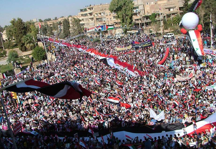"""EDS NOTE--RESTRICTED TO EDITORIAL USE - MANDATORY CREDIT """"AFP PHOTO / SANA"""" - NO MARKETING NO ADVERTISING CAMPAIGNS - DISTRIBUTED AS A SERVICE TO CLIENTS- A handout picture released by the Syrian Arab News Agency (SANA) shows Syrians waving national flags as they rally in support of President Bashar al-Assad in the city of Deir Al-Zor, southeast of Damascus on November 1, 2011.  AFP PHOTO/HO-SANA (Photo credit should read -/AFP/Getty Images) Photo: -, AFP/Getty Images"""
