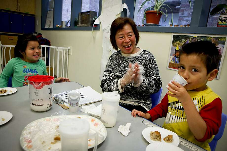 "Maria Corazon Chu aka ""Grandma Cora"" and Lucy Calderon, 4, applaud after 4-yr. old Andy Nic Navarrete poured milk in his cup on Tuesday, Oct. 4, 2011 in San Francisco, Calif.  Maria Corazon Chu aka ""Grandma Cora"" and Eduardo Chu aka ""Grandpa Eddy"" are volunteers at the Compass Children's Center in San Francisco, Calif. Photo: Russell Yip, The Chronicle"