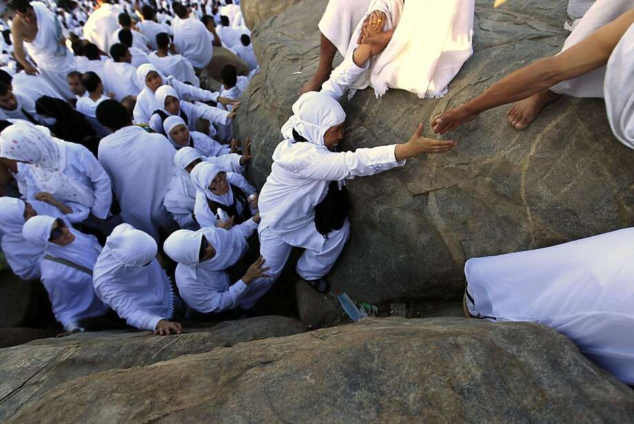 Muslim pilgrims climb a rocky hill called the Mountain of Mercy, on the Plain of Arafat near Mecca, Saudi Arabia, Saturday, Nov. 5, 2011. The annual Islamic pilgrimage draws 2.5 million visitors each year, making it the largest yearly gathering of people in the world. (AP Photo/Hassan Ammar) Ran on: 11-06-2011 Muslim pilgrims climb a rocky hill called the Mountain of Mercy, on the Plain of Arafat near Mecca, Saudi Arabia, at the start of the five-day hajj that draws 2.5 million people each year. Photo: Hassan Ammar, AP
