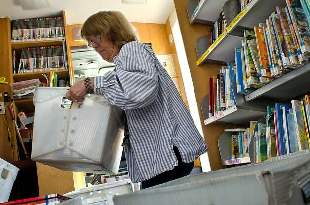 Librarian Terry Jones stacks bins full of books before driving the Marin County Free Library Bookmobile to her next stop in Tomales, California on October 19, 2011. Ms. Jones drives the Bookmobile to provide library services for rural communities, including three one-room schoolhouses, in northern Marin County. Photo: Alvin Jornada, Special To The Chronicle
