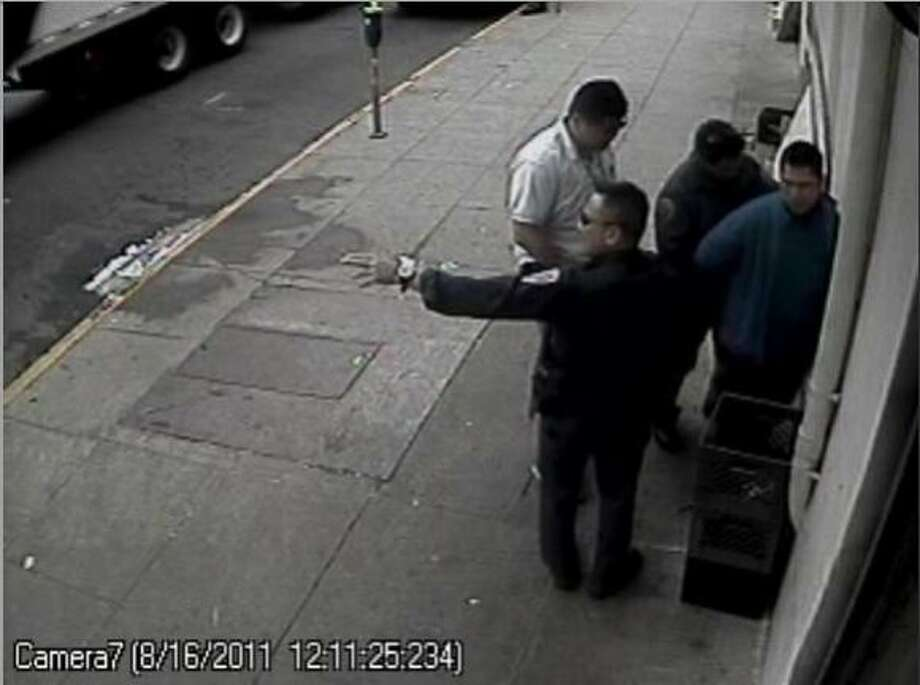 Surveillance footage released at a news conference at the Public DefenderÍs office allegedly shows police using excessive force during an August 16, 2011 call regarding two men arguing outside a Richmond District market. The video shows officers interrogating, and eventually handcuffing and searching market owner Charles Tran, shown pressed against a wall to the right, 44, who was not involved in the fight and has no criminal history. Photo: Courtesy Of The San Francisco Pu