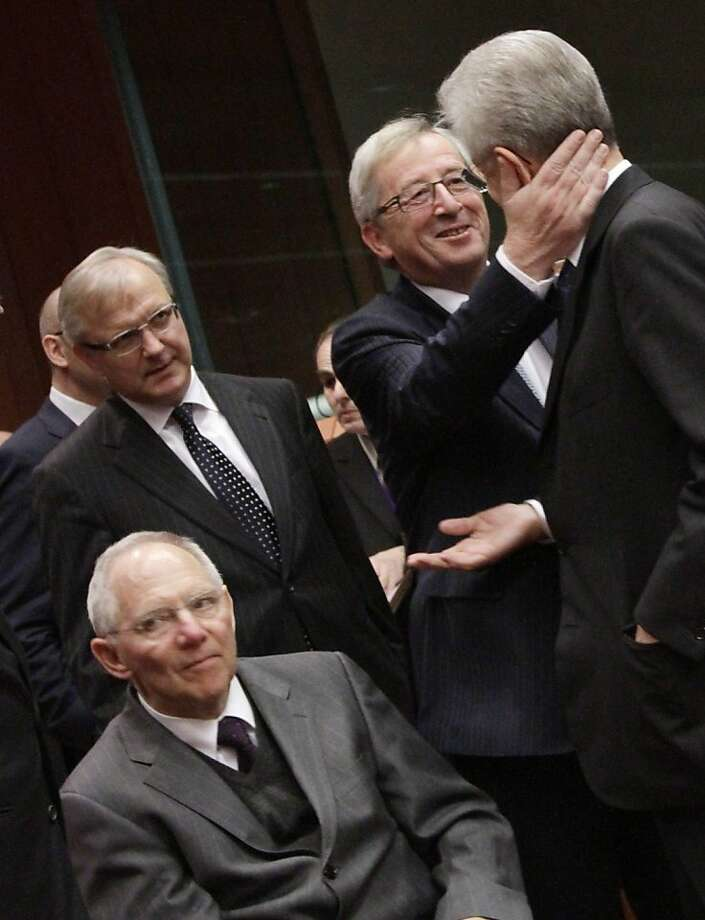 From left, European Commissioner for the Economy Olli Rehn, German Finance Minister Wolfgang Schaeuble, Luxembourg's Prime Minister Jean-Claude Juncker and Italian Prime Minister and Finance Minister Mario Monti greet each other during a round table meeting of the eurogroup at the EU Council building in Brussels on Tuesday, Nov. 29, 2011. The 17 finance ministers of countries that use the euro converged on EU headquarters Tuesday in a desperate bid to save their currency and to protect Europe, the United States, Asia and the rest of the global economy from a debt-induced financial tsunami. (AP Photo/Virginia Mayo)  Ran on: 11-30-2011 European Commissioner for the Economy Olli Rehn (left), German Finance Minister Wolfgang Schaeuble, Luxembourg leader JeanClaude Juncker and Italian leader Mario Monti meet in Brussels. Photo: Virginia Mayo, AP