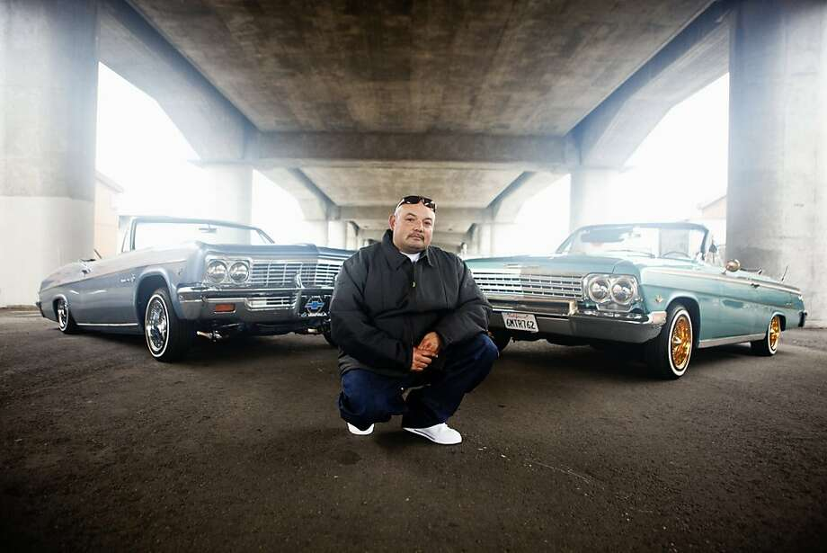 Frankie Suarez with his two cars.  lime green 62 Impala convertible, sky blue 66 Impala convertible (Padrinos CC), part of Trevor Traynor's exhibition focused on lowriders. Photo: Trevor Traynor