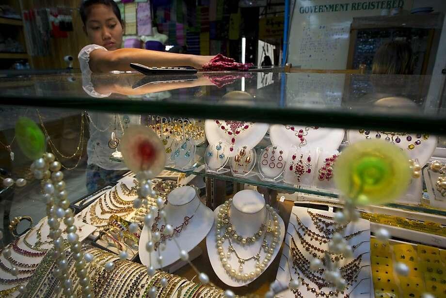 A worker cleans up a showcase of a jewelry shop at Aung San Market in downtown Yangon, Myanmar, Tuesday, Nov. 29, 2011. (AP Photo/Vincent Thian) Photo: Vincent Thian, AP