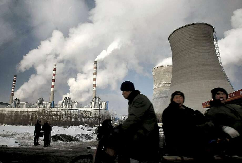 FILE - In this Friday, Dec. 17, 2010 file photo, workers cycle past a coal-fired power plant on a tricycle cart in Changchun, in northeast China's Jilin province. The world's emissions of heat-trapping carbon dioxide took the biggest jump on record, the U.S. Department of Energy calculated, a sign of how feeble the world's efforts are at slowing man-made global warming. The new figures for 2010 mean that levels of greenhouse gases are higher than the worst case scenario outlined by climate change experts just four years ago. China, the United States and India are the world's top producers of greenhouse gases. Tom Boden, director of the Energy Department's Carbon Dioxide Information Analysis Center at Oak Ridge National Lab, said that in 2010 people were traveling, and manufacturing was back up worldwide, spurring the use of fossil fuels, the chief contributor of man-made climate change. (AP Photo) Photo: AP