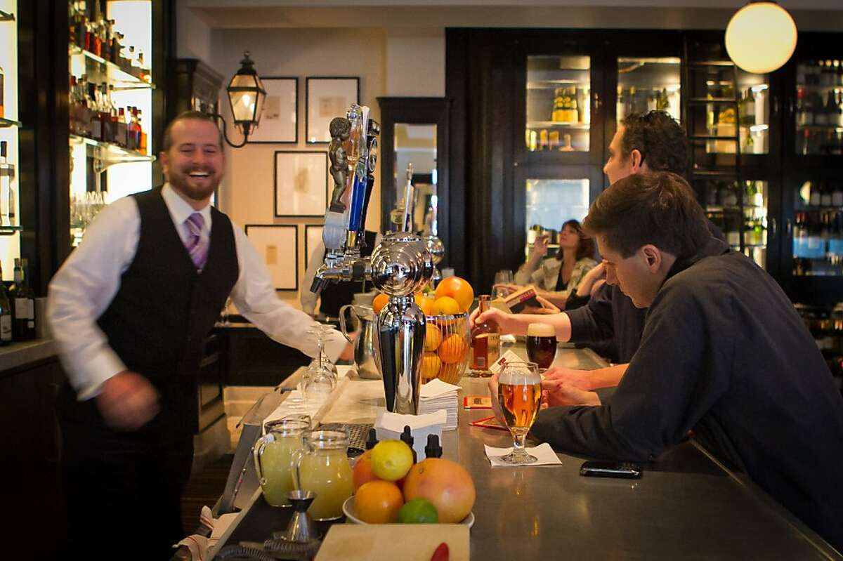 Bartender Brandon Clements has a laugh with customers at Cafe Des Amis in San Francisco, Calif., on Tuesday, November 1, 2011.