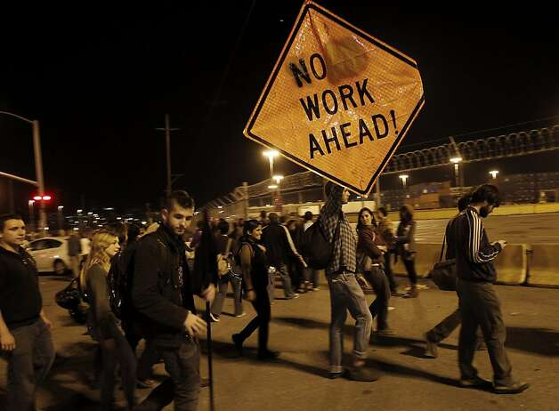 A protester modified a construction sign to get his point across at the port. Thousands of OccupyOakland supporters left their downtown protest for the Port of Oakland where they met little resistance early in the evening Wednesday November 2, 2011. They essentially shut it down by blocking entrances at the port. Photo: Brant Ward, The Chronicle