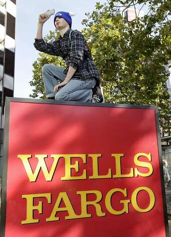A man snaps a photograph of Occupy Oakland protesters that temporarily shut down a Wells Fargo branch at 12th and Broadway streets during a general strike in Oakland, Calif. on Wednesday, Nov. 3, 2011. Photo: Paul Chinn, The Chronicle