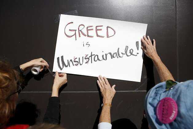 "Protestors tape a sign depicting ""Greed is Unsustainable"" to the exterior of a Wells Fargo Bank in downtown Oakland on Wednesday, November 2, 2011 in Oakland, Calif. Photo: Beck Diefenbach, Special To The Chronicle"