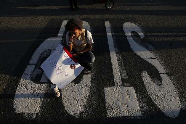 A young protester who declined to give her name, sits in the intersection as thousands others converged on the Port of Oakland. Occupy Oakland protesters numbering in the thousands shut down the Port of Oakland on Wednesday, November 2, 2011, during the General Strike. Photo: Carlos Avila Gonzalez, The Chronicle