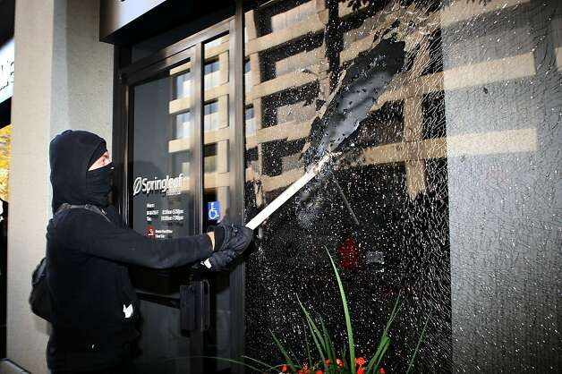 A protester breaks the windows of Springleaf financial bank on Webster St. during the afternoon march of the General Assembly of Occupy Oakland in Oakland, Calif., on Wednesday, November 2, 2011. Photo: Liz Hafalia, The Chronicle