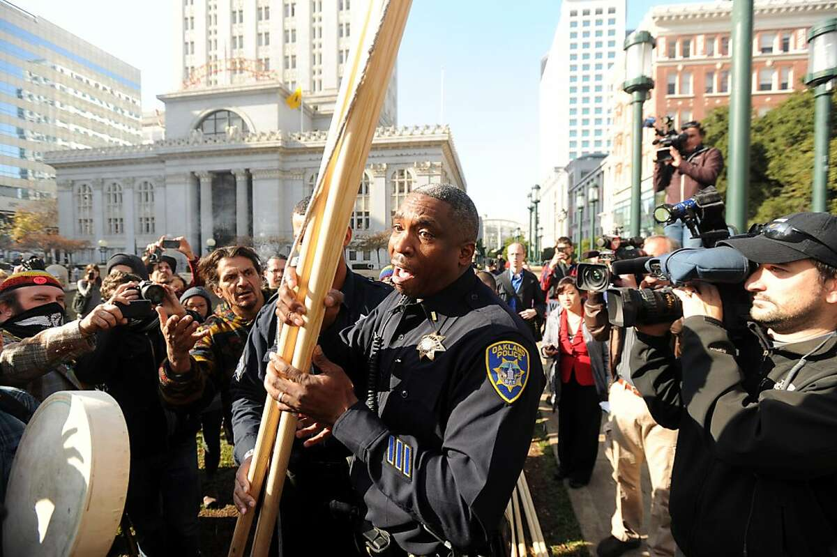 Oakland police Lt. F. Hamilton confiscates wood framing from protester Zachary RunningWolf, left, after he tried to erect a teepee near Oakland, Calif., City Hall on Tuesday, Nov. 29, 2011. After more than an hour of wrangling between an Occupy Oakland lawyer, police officers and city administrators, RunningWolf built the teepee with the understanding that he'd remove it each night.