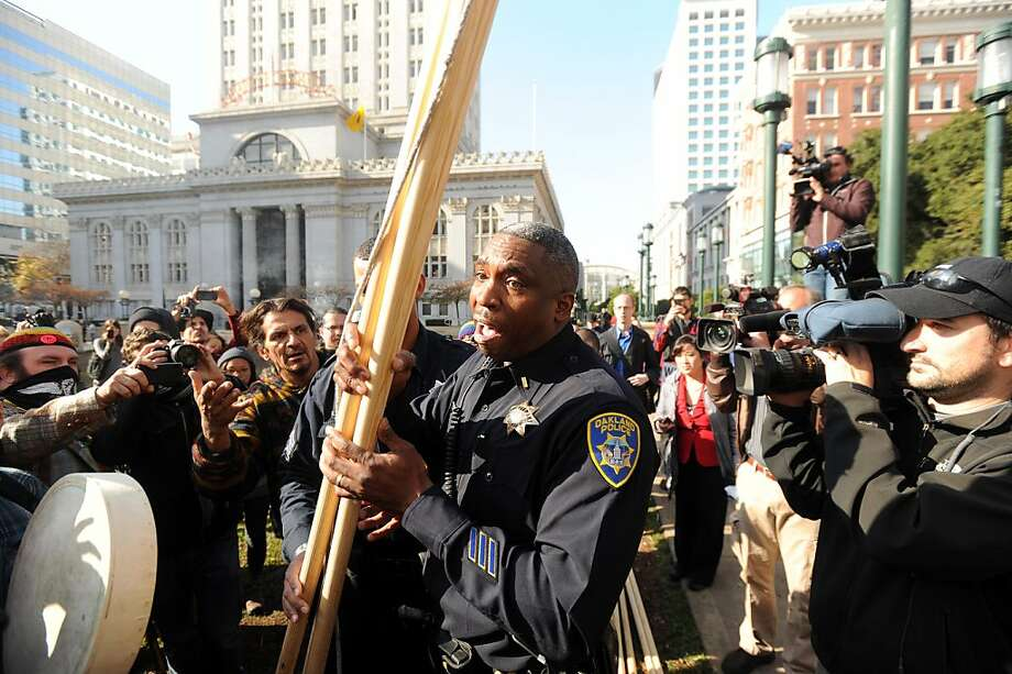 Oakland police Lt. F. Hamilton confiscates wood framing from protester Zachary RunningWolf, left, after he tried to erect a teepee near Oakland, Calif., City Hall on Tuesday, Nov. 29, 2011. After more than an hour of wrangling between an Occupy Oakland lawyer, police officers and city administrators, RunningWolf built the teepee with the understanding that he'd remove it each night. Photo: Noah Berger, Special To The Chronicle