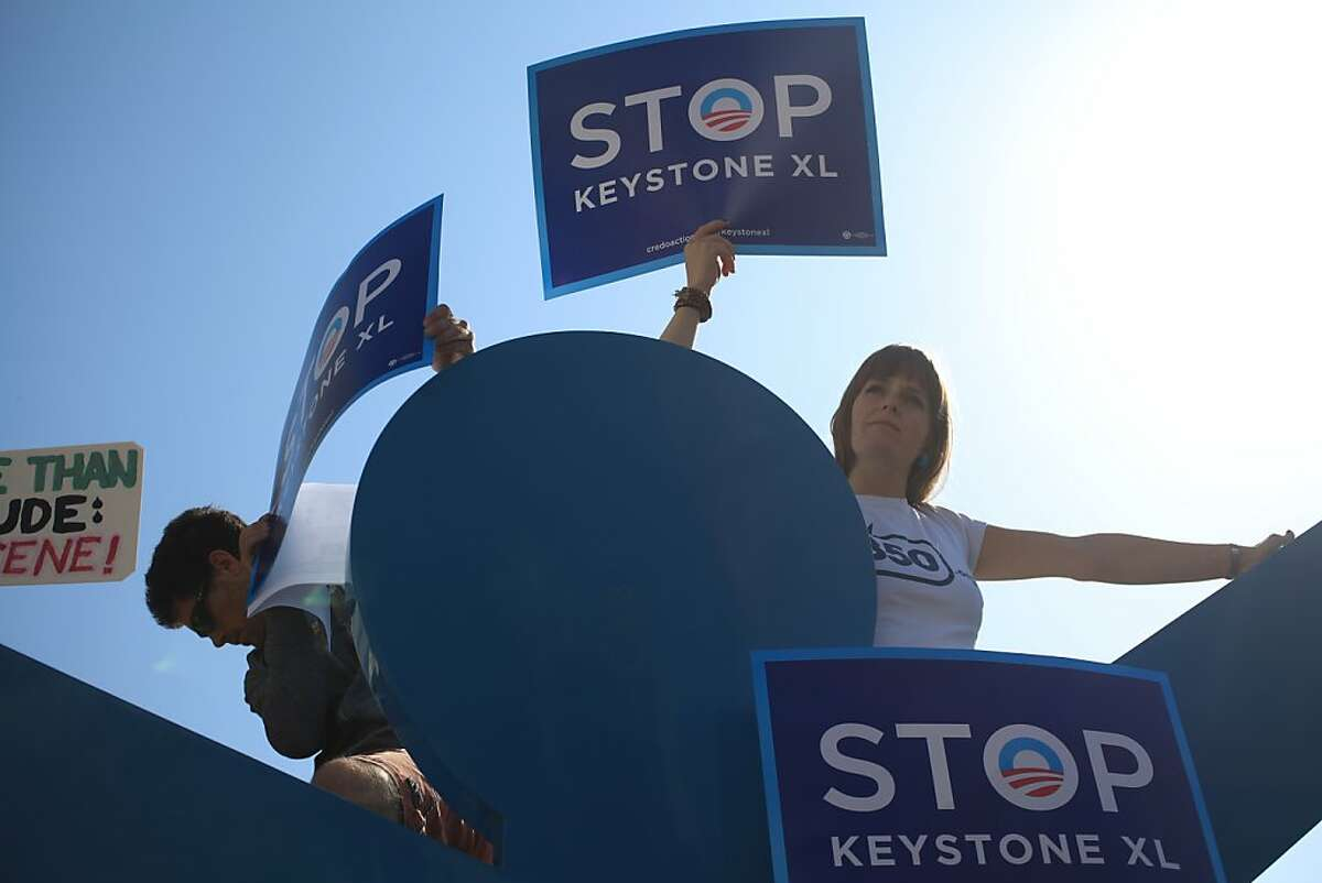 Josh Newman and Amanda Ravenhill, both of San Francisco stand atop a Keith Harring sculpture holding signs protesting the proposed Keystone XL pipeline project outside the W Hotel, where the president attended a fundraiser in San Francisco, Calif. on Tuesday, October 25, 2011.
