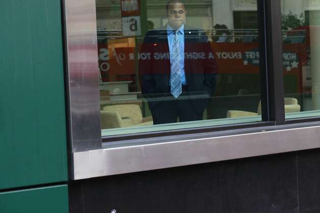 Giovanni Gourgue, a security guard at Fidelity Investments, watches as a group of protesters connected to Occupy San Francisco march through the financial district on Monday October 24, 2011 in San Francisco, Calif. Photo: Mike Kepka, The Chronicle