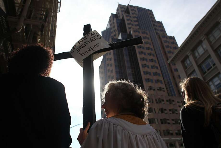"Hope Attenhofer, a seminarian at the Pacific School of Religion, holds a cross to the sky during an Occupy San Francisco march through the financial district on Monday October 24, 2011 in San Francisco, Calif. ""We're called to be here,"" said Attenhofer, ""There is too much corporate greed that is leaving people hungry and without hope or jobs."" Photo: Mike Kepka, The Chronicle"