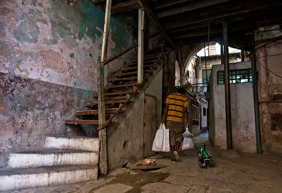 A Cuban arrives at his dilapidated house, on November 3, 2011 in Havana. The Cuban government has approved a law allowing individuals to buy and sell homes for the first time in 50 years, the official newspaper Granma said on 3 November, 2011. The measure is part of a series of economic reforms aimed at reviving the economy of the communist-ruled island and easing a severe housing shortage.  AFP PHOTO/STR (Photo credit should read STR/AFP/Getty Images) Photo: Str, AFP/Getty Images