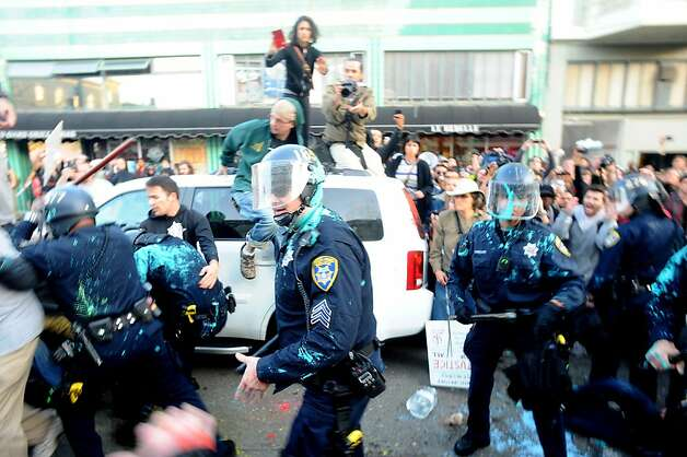 Paint-splattered police officers hold off an angry crowd as they surround detained protesters on Tuesday, Oct. 25, 2011, in Oakland, Calif. Photo: Noah Berger, Special To The Chronicle