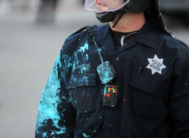 Oakland police officer Lawless stands covered in paint after a confrontation with Occupy Oakland protesters on Tuesday, Oct. 25, 2011, in Oakland, Calif. Protesters threw paint, vinegar and water at officers while marching through downtown. Photo: Noah Berger, Special To The Chronicle