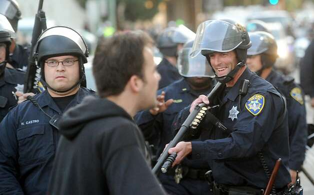 A police officer raises a weapon at demonstrators during an Occupy Oakland demonstration on Tuesday, Oct. 25, 2011, in Oakland, Calif. Photo: Noah Berger, Special To The Chronicle