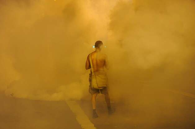 aN Occupy Oakland protester walks into a cloud of teargas on Tuesday, Oct. 25, 2011, in Oakland, Calif. Photo: Noah Berger, Special To The Chronicle