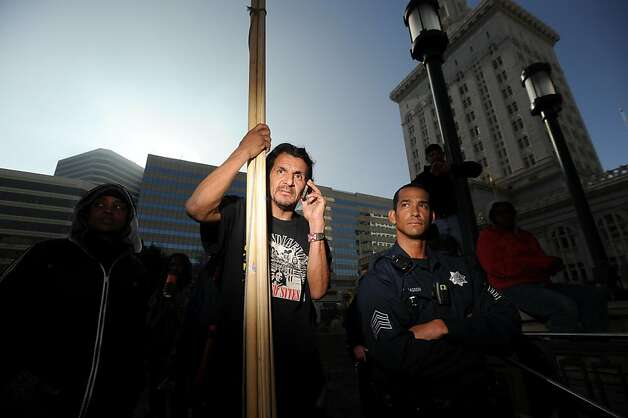 Protester Zachary RunningWolf holds wood framing while involved in a standoff with police over whether he could erect a teepee near Oakland, Calif., City Hall on Tuesday, Nov. 29, 2011. After more than an hour of wrangling between his lawyer, police officers and city administrators, RunningWolf built the teepee with the understanding that he'd remove it each night. At right is police Sgt. R. Holmgren.  Ran on: 11-30-2011 Zachary RunningWolf (left) and police Sgt. R. Holmgren participate in negotiations over RunningWolf's plan for a teepee. He was allowed to build it but must remove it every night. Ran on: 11-30-2011 Zachary RunningWolf (left) and police Sgt. R. Holmgren participate in negotiations over RunningWolf's plan for a teepee. He was allowed to build it but must remove it every night. Photo: Noah Berger, Special To The Chronicle