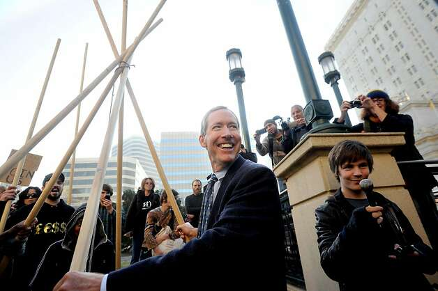 Kirk Boyd, an attorney representing Occupy Oakland, carries a teepee to a spot outside Oakland, Calif., City Hall on Tuesday, Nov. 29, 2011. After more than an hour of wrangling between protester Zachary Runningwolf, police officers and city administrators, RunningWolf was allowed to build the teepee with the understanding that he'd remove it each night. Photo: Noah Berger, Special To The Chronicle