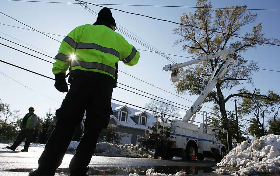 A police officer directs traffic as a work crew repairs power lines in South Hadley, Mass., Sunday, Oct. 30, 2011. Millions of people from Maine to Maryland are without power after an unseasonably early nor'easter dumped heavy, wet snow over the weekend on a region more used to gaping at leaves in October than shoveling snow.  (AP Photo/Michael Dwyer) Photo: Michael Dwyer, AP
