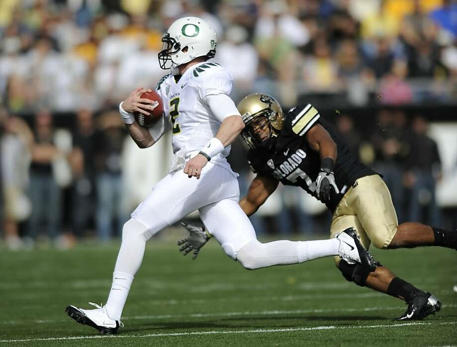 Oregon quarterback Bryan Bennett runs against Colorado defensive back Anthony Perkins (7) during the first half of an NCAA football game in Boulder, Colo., Saturday, Oct. 22, 2011. (AP Photo/Jack Dempsey)  Ran on: 10-31-2011 Oregon redshirt freshman quarterback Bryan Bennett at times has outshone the Ducks' regular starter, Darron Thomas. Photo: Jack Dempsey, AP